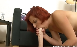Redhead rotates between mouth and pussy with huge dildo